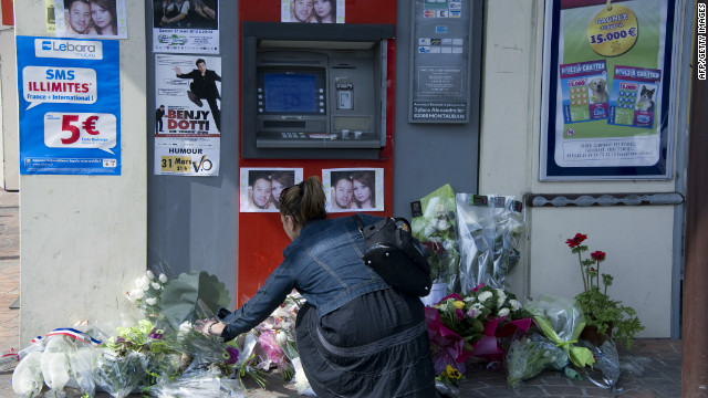 A woman places a bouquet of flowers on March 17, at the site where two French soldiers were killed on March 15, in the French city of Montauban.