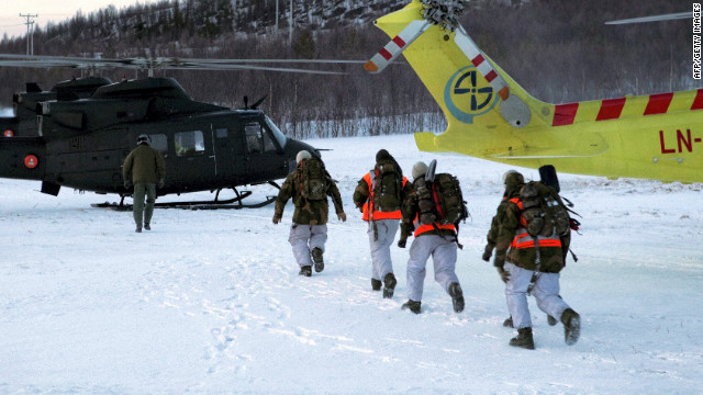 Rescuers hurry toward helicopters after a deadly avalanche Monday outside Kafjord, Norway.