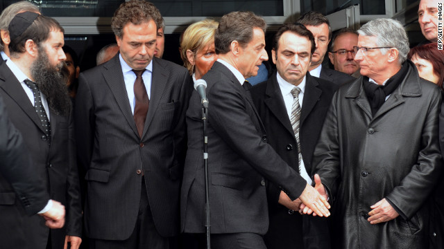 French President Nicolas Sarkozy shakes hands with the mayor of Toulouse at the Ozar Hatorah school. Sarkozy flew to Toulouse on Monday, after the school shooting took place. He declared &quot;everything must be done so the killer is arrested.&quot;