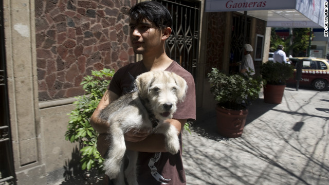 A young man carries his dog out of his home in Mexico City. 