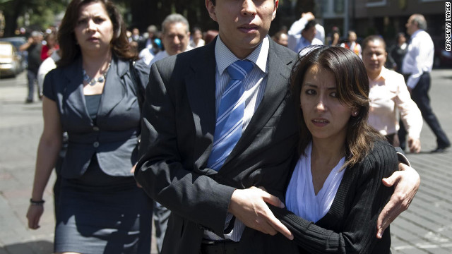 A man helps a woman to safety in Mexico City.