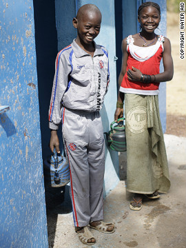 Yacouba Doumbia (left) and a friend outside a latrine block at Simba East school in the Tienfala commune, Mali.