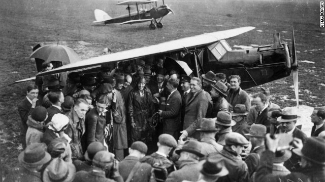 Amelia Earhart is surrounded by well-wishers after completing the first solo transatlantic flight by a woman, landing in Northern Ireland in 1932.