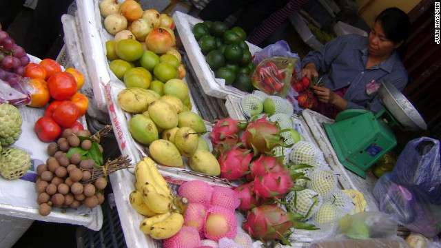 A vendor sells tropical fruits such as cherimoya, lychee and dragon fruit at an open air market in Hoi An.