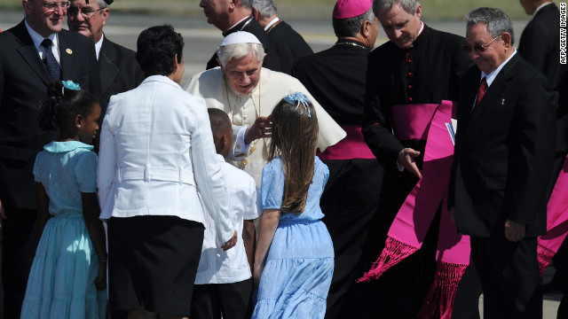 Pope Benedict XVI is welcomed by children as Cuban President Raul Castro looks on upon arrival to Santiago de Cuba on Monday, March 26. Fourteen years after Pope John Paul II visited Cuba, Pope Benedict is making his first trip to the communist country.