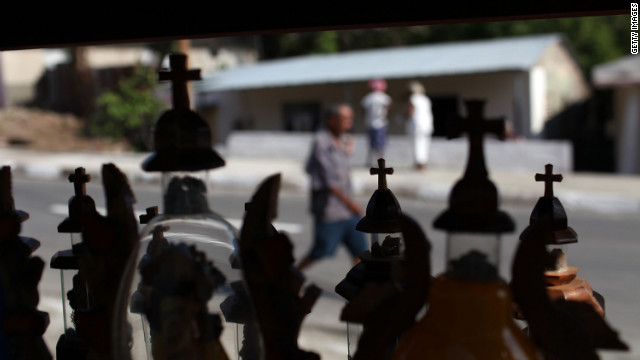 People walk by religious items for sale at Basilica del Cobre, the shrine to Our Lady of Charity of El Cobre, Cuba's patron saint on March 25.