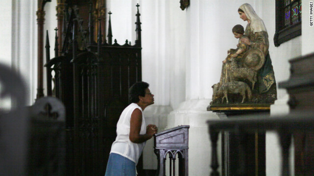 A woman prays before the start of services at Santo Angel Custodio church.