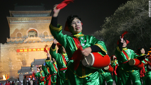 A women's drum troupe performs in front of Beijing's ancient Bell Tower, used for time keeping in Beijing for centuries.