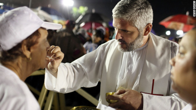 Cubans take communion during the mass of Pope Benedict XVI in Revolution Square.