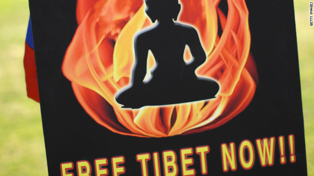 The sign held by a demonstrator who is protesting Chinese occupation and policies in Tibet refers to self-immolations in Tibet.