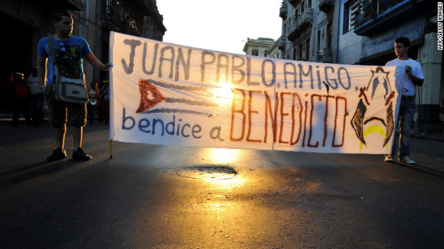 Two youngsters hold a banner -- &quot;John Paul friend, bless Benedict&quot; -- during a procession of Our Lady of Charity through the streets of Havana.