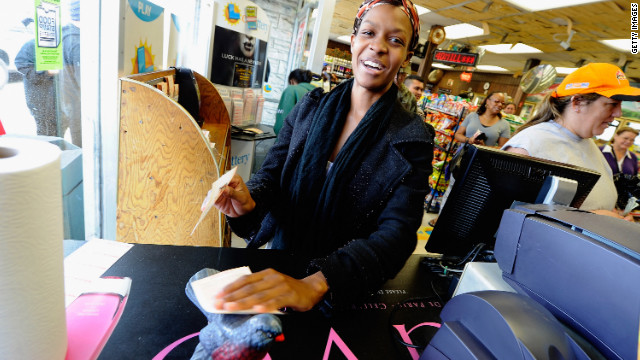 Jasmine Covington, like many Bluebird customers, rubs her Mega Millions ticket against the store's wooden Bluebird statuette for good luck.
