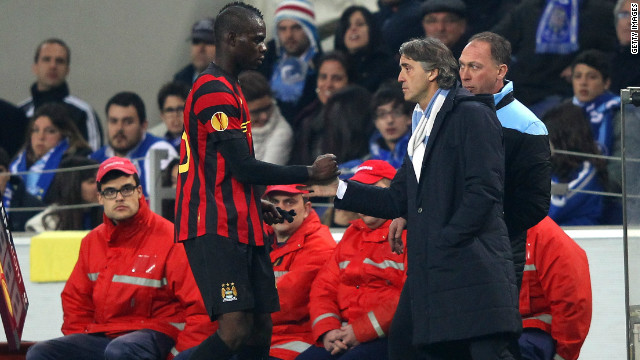 Mario Balotelli shakes hands with manager Roberto Mancini after being substituted in the Europa League tie at Porto.