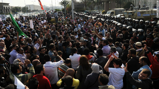 Egyptian protesters gather opposite riot police during a demonstration in Cairo on March 24, 2012.