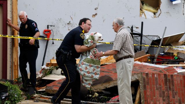 A police officer in Arlington returns a dog to David Lowe after it was rescued from the rubble of his daughter's home.