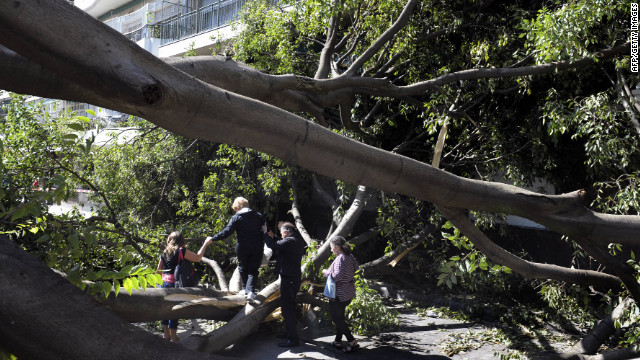 People try to get past a tree that fell during a storm in Buenos Aires on Wednesday night. At least 13 people were killed.