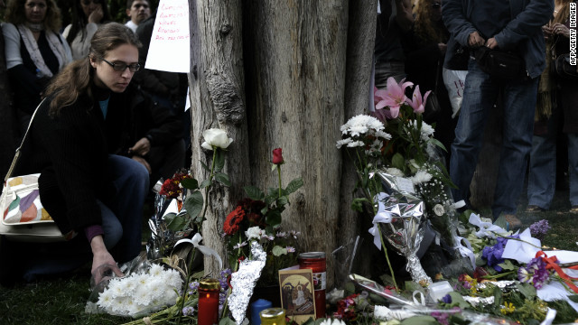 People lay flowers at the site where an elderly man shot himself at Syntagma square in Athens on April 4, 2012.