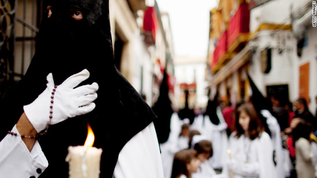 A penitent of the Perdon brotherhood walks during a Holy Week procession in Cordoba, Spain.