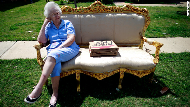 Nelda Vines sits in a chair in the front lawn of a home while waiting for several family members who were visiting a tornado-ravaged neighborhood.