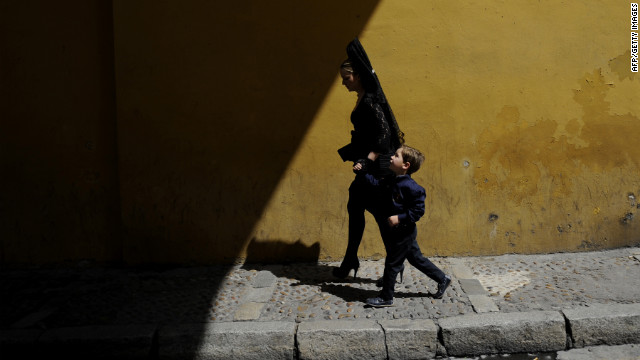 A woman and child walk under the Macarena Arch in Sevilla, Spain.