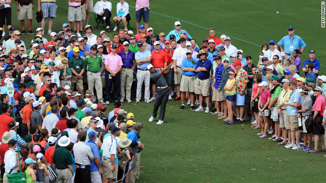 Tiger Woods hits a shot on the ninth hole in front of a gallery of patrons during the first round of the 2012 Masters Tournament.