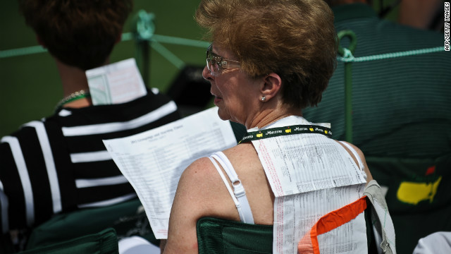 A woman uses a start list to protect herself from the sun during Thursday's opening round.