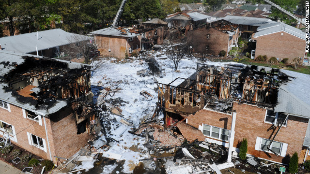 Fire suppression foam covers wreckage and debris near the burned-out apartments.