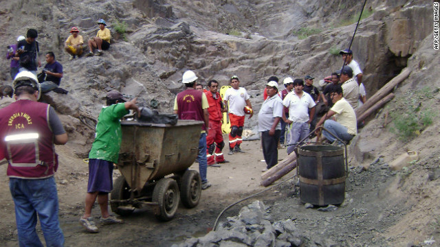 Workers walk toward the entrance of a mine east of Ica, Peru, on Friday in an attempt to rescue nine trapped miners.