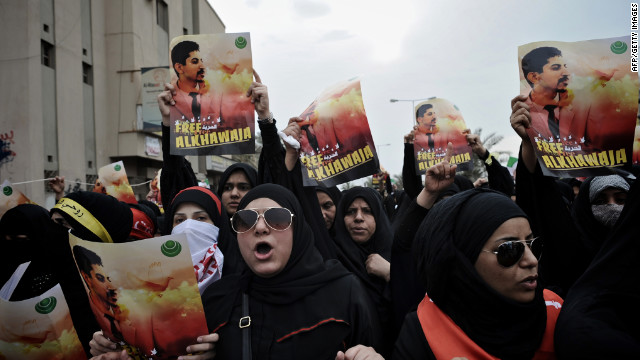 Bahraini Shiite demonstrators hold posters of jailed activist Abdulhadi al-Khawaja during a protest calling for his release in the village of Jidhafs, west of Manama, on April 6, 2012. 