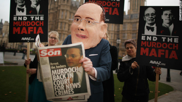  A protester poses as James Murdoch reading a spoof newspaper following allegations of hacking at News International in 2011