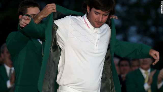 Bubba Watson receives the green jacket from 2011 winner Charl Schwartzel of South Africa.