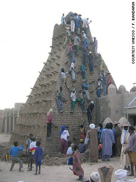 People climb the mosque. The buildings are important sources of income to Timbuktu locals, drawing tourists from around the world, but the fighting is expected to lead to a collapse of the industry.