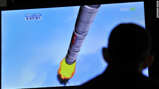 South Koreans at a train station in Seoul watch a TV screen showing a graphic of North Korea's rocket launch Friday.