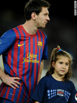 Three-time world player of the year Lionel Messi with a mascot wearing an anti-racism shirt ahead of Barcelona's UEFA Champions League match against Czech team Viktoria Plzen in October 2011.