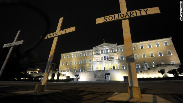 "Crosses reading ""Solidarity,"" ""Dignity""' and ""Freedom"" are placed before Greek parliament during a gathering at Syntagma Square on April 8, 2012. Protesters gathered after the suicide of pensioner Dimitris Christoulas, who cited austerity measures as a reason."