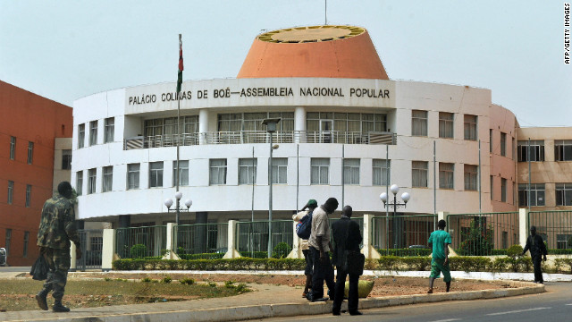 Residents walk past parliament in Bissau last month. Military forces are in the streets of the capital Friday.