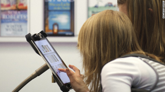 People looking at an e-book reader app on the Apple iPad.