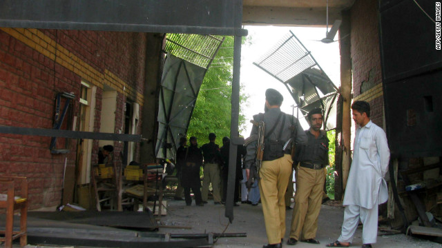 Pakistani security officials gather at the damaged entrance of a prison after an attack by militants in Bannu on April 15, 2012.