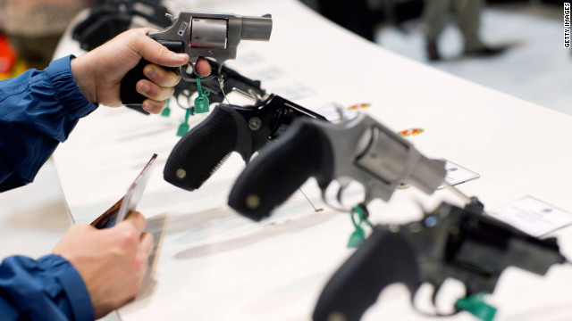 A visitor looks at a Taurus revolver during the National Rifle Association's annual meeting Friday in St. Louis.