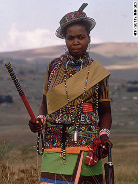 A young Zulu woman, wearing samples of her colorful beadwork, poses en route to a traditional wedding.