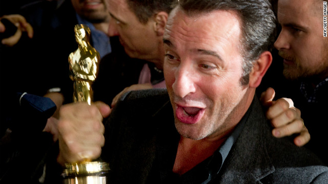 Jean Dujardin holds his Oscar for &quot;The Artist,&quot; but will it offset for the loss of France's triple-A credit rating?