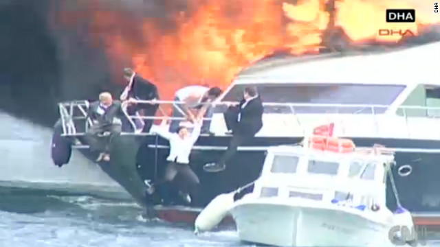 Well-dressed passengers escape a yacht that caught fire Wednesday in the Bosporus during a storm in Istanbul, Turkey.