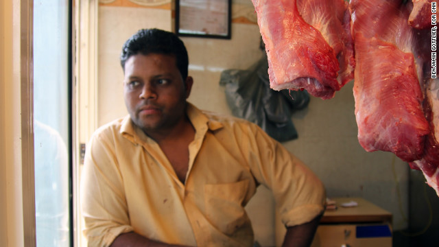The cashier at Qureshi's butchery looks out his window in Nizamudin, Delhi, on March 12.