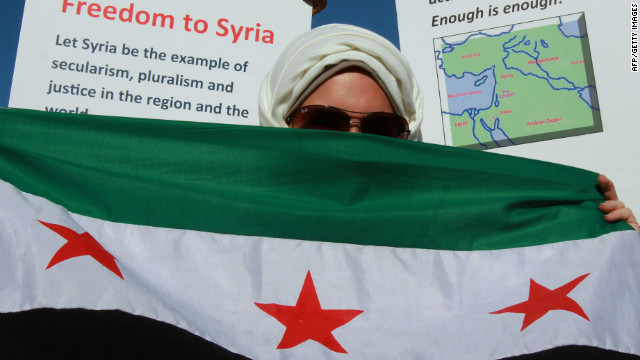 An anti-Syria government protester with a pre-Baath Syrian flag, which has been adopted by the opposition movement.