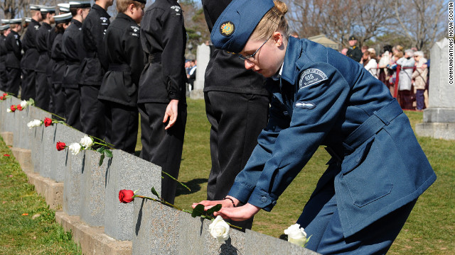 A young cadet places a rose on the headstone of one of the Titanic gravesites during a Titanic Spiritual Ceremony at the Fairview Lawn Cemetery in Halifax.