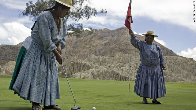 An indigenous Aymara woman plays an approach shot as her colleague holds the flag at La Paz Golf Club in Bolivia. It is considered to be the highest course in the world, with its layouts ranging from 3,277 to 3,342 meters above sea level.