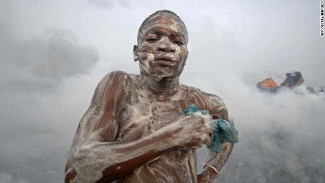 A man soaps himself on a dump after a day's work in Lagos. Olusosun Landfill Site is Nigeria's largest rubbish dump dealing with 2,400 metric tons of rubbish every day. A whole community lives on the dump, collecting scrap to trade for cash.