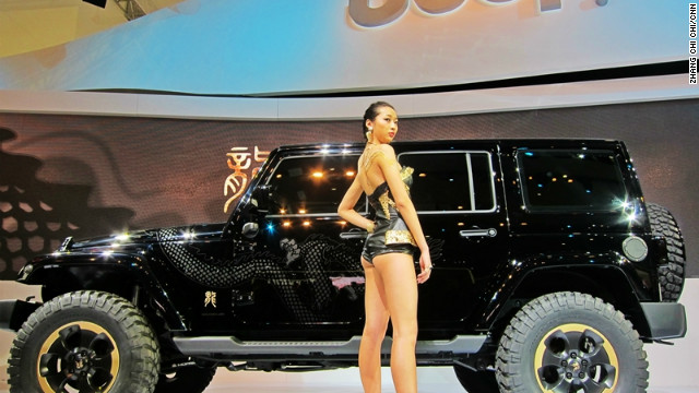 A model stands in front of a limited edition Jeep, designed with a dragon logo especially made for the China market - a first for Jeep.