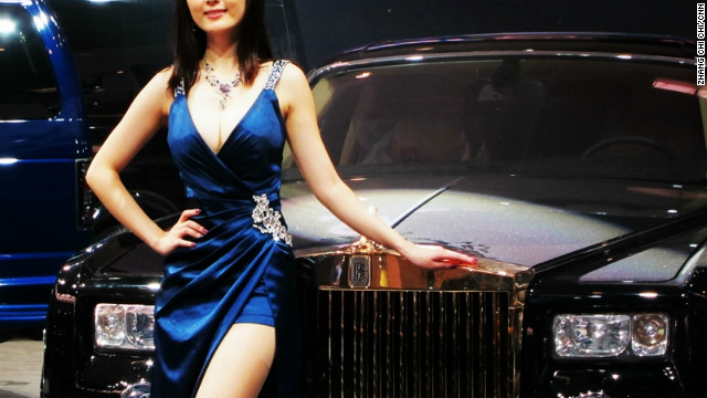 A woman models in front of a Rolls Royce model shown at the Auto China, in a country that is its largest market in the world.