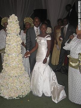 A newlywed Nigerian couple cut their extravagant wedding cake, surrounded by guests in traditional attire.
